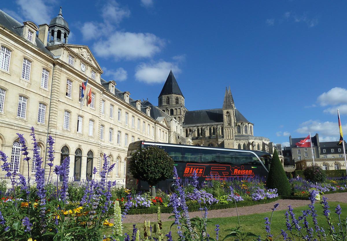 Ein Blitz-Bus vor dem Schloss L'Abbaye aux Hommes in Cae in der Normandie