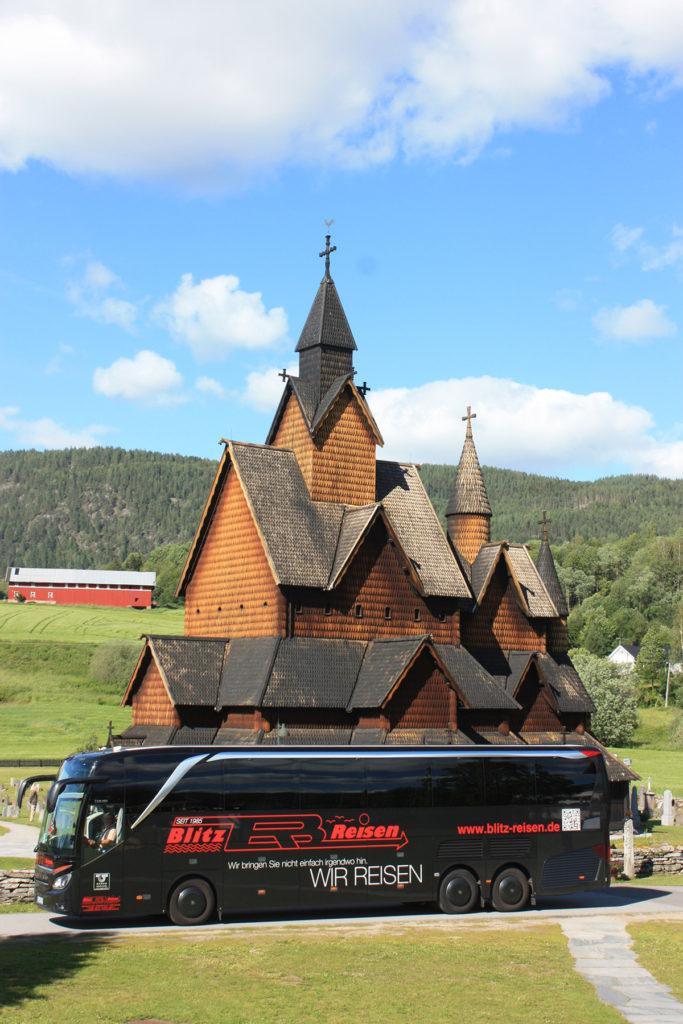 Ein Blitz-Bus vor der Stabkirche von Heddal in der Telemark in Norwegen