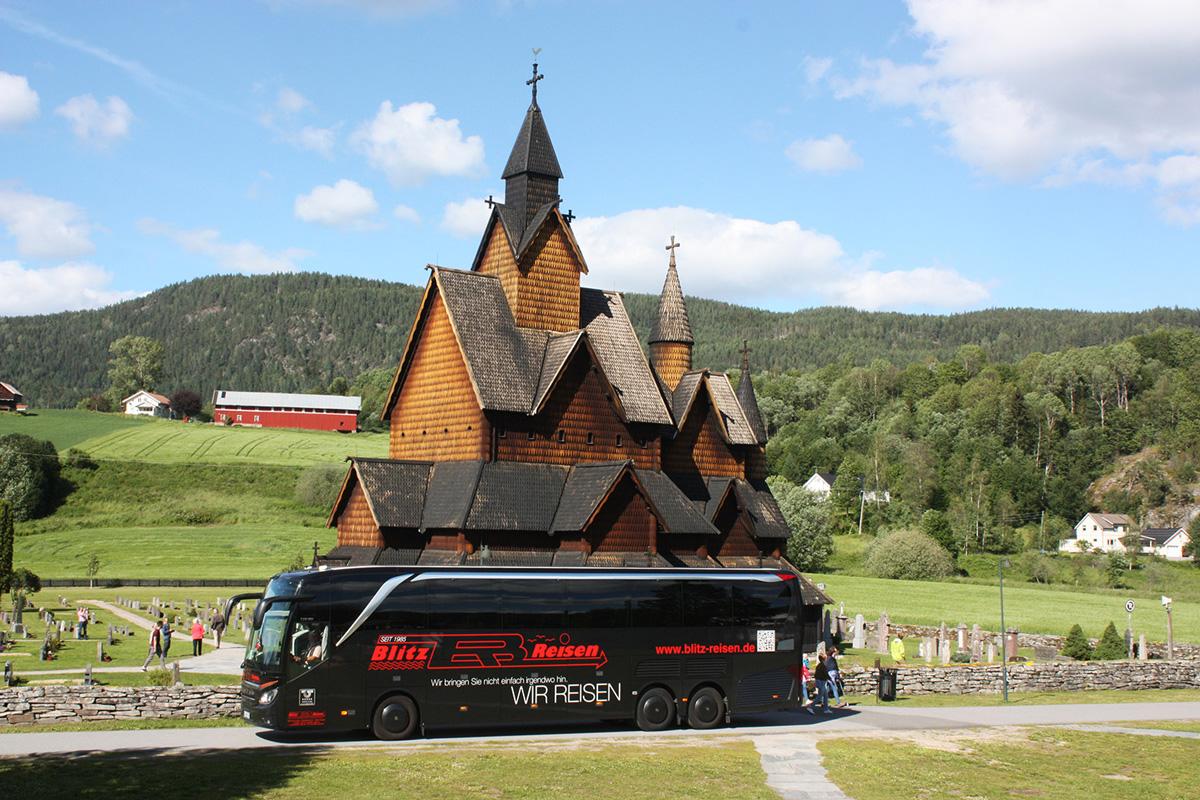 Ein Blitz-Bus vor der Stabkirche von Heddal in der Telemark