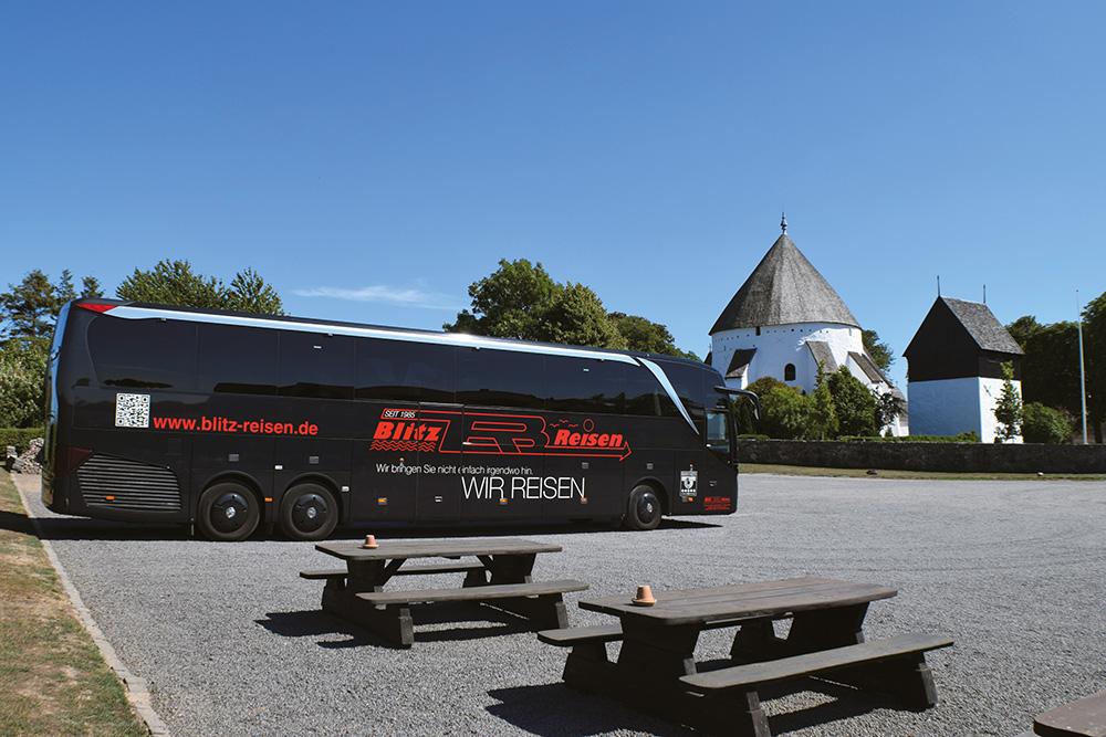 Ein Blitz-Bus vor einer der für Bornholm so typischen Rundkirchen
