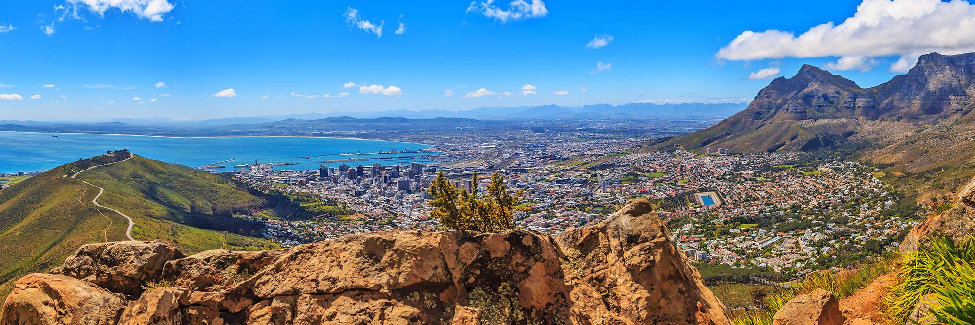Panoramaaufnahme von Kapstadt und Tafelberg sowie Signal Hillaufgenommen vom Lions Head tagsüber bei blauem Himmel mit einigen weißen Wolken fotografiert in Südfrika im September 2013